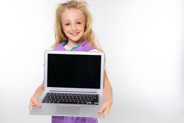 portrait of a blond child in a casual look showing a laptop display with a mockup on a white background