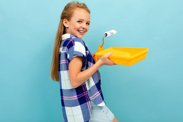 Caucasian girl paints a wall with a roller and paint isolated on blue background