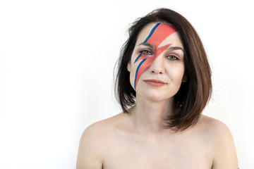 red and blue lightning bolt on her beautiful face. Beautiful girl with original make-up on a white background. Studio photo
