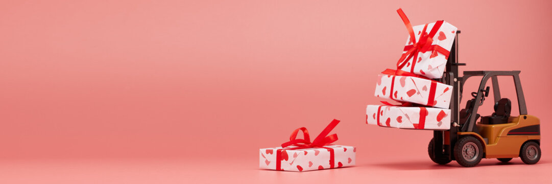 Forklift and gift boxes on pink background with copy space. Valentine's Day.