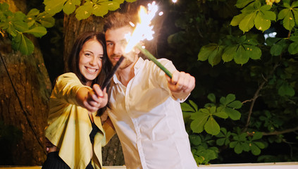 A luxury couple in cafe at night with firework sparklers.