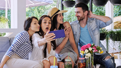 Group of friends makes selfie in at cafe