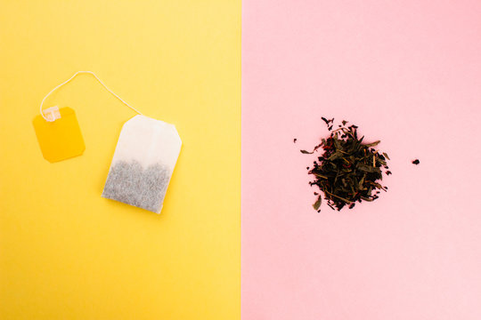 Tea bag and loose leaf tea flat lay on colorful trendy yellow and pink backgrounds. Top view copy space. Tea bag or loose leaf tea waste and recycle concept. Creative design for articles. Stock photo