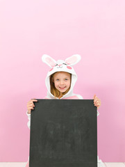 pretty blonde girl with cozy rabbit costume and blackboard is posing in the studio and is happy in front of pink background