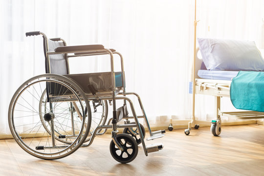 Empty wheelchair and bed in patient room, in hospital.