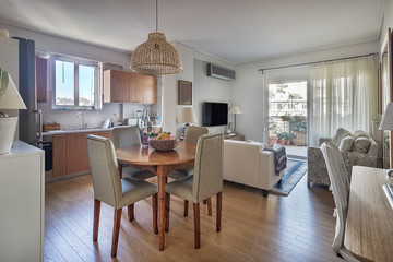 Open-concept of a kitchen, dining wooden table and living room with balcony in a very small apartments.