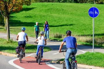 Radfahrer befahren einen Übergang von der Straße auf einen kombinierten Rad- und Fußweg