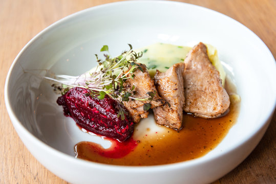 Delicious roasted pork filet cooked with smashed potatoes and smashed beetroots served in white plate.