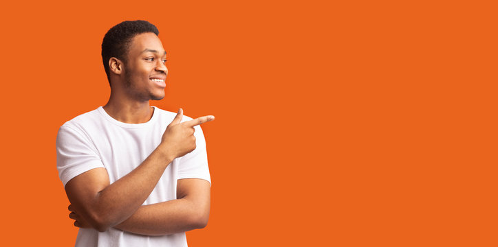 Young black man pointing at copy space with thumb up