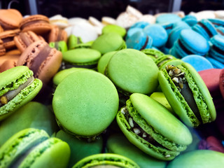 many colorful macarons biscuits arranged disorderly