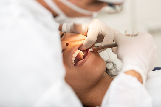 Young woman being seen in a dentist's office. Concept of toothache, wisdom tooth extraction, anesthesia, problems with caries or gums. Oral health care. Dentist day.
