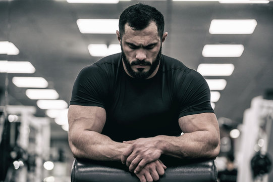 mental mind sport motivation concept of young handsome strong man with beard wearing black jersey concentration relaxation in sport gym