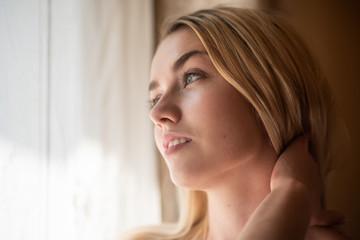 Teenage woman looking outside through window