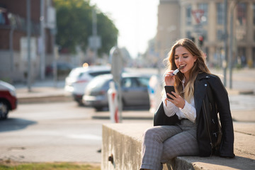 Teen girl looking at smartphone screen, urban background.