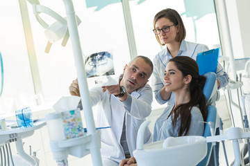 Dentist and his assistant in dental office talking with young female patient and preparing for...