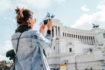 Young alone caucasian female tourist taking a photo of Victor Emmanuel II Monument using a modern smartphone on Piazza Venezia in Rome, Italy. Fotomurales