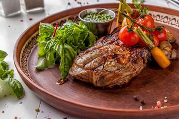 Canvas Prints Pork entrecote served with grilled vegetables, mushrooms and pesto sauce, restaurant dish, Horizontal orientation