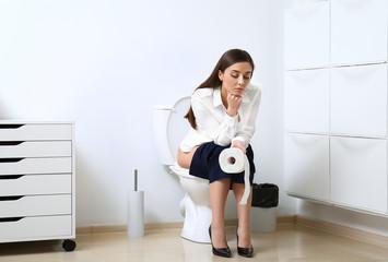 Upset woman sitting on toilet bowl in bathroom