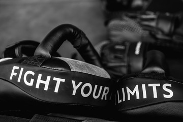 Close up of FIGHT YOUR LIMITS word on black boxing and kicking practice pad. Motivational and...