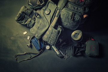 The backpack of a military medic stands on a green background. Around lies a first aid kit and various doctor tools. View from above.