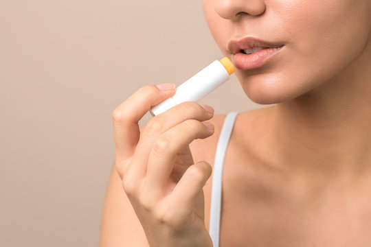 lips care and protection. woman applying balm on lips