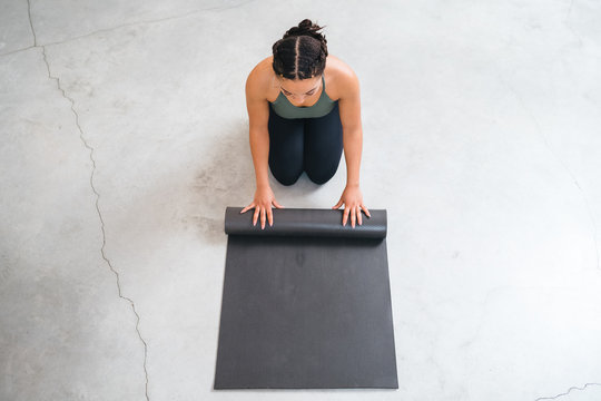 Top view of a beautiful young woman while rolling up the mat used for yoga on a white concrete floor - Copy space - Millennial during a moment of relax and personal well-being