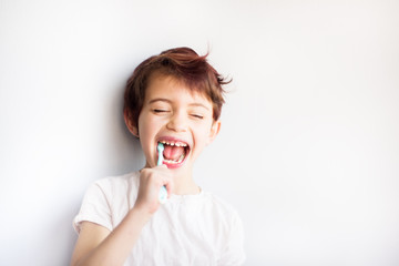 Horizontal portrait of child with closed eyes brushing teeth with blue and white toothbrush. Dental and health care from childhood. Healthy changing teeth on smiling face. Copy space for text