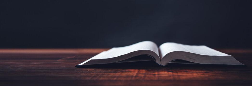 open book on wooden desk background