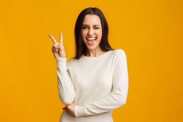 Playful brunette girl showing peace sign and winking on yellow background