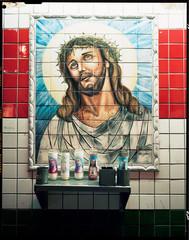 Tiled portrait of Jesus Christ above prayer candles on metal shelf