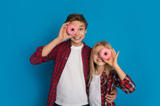 Happy siblings covering eyes with donuts, posing together over blue background