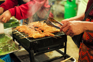 Closeup row of meat sausages on the metal grill with motion blurred hands and seller in background