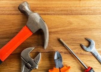 High angle shot of a hammer, a screwdriver and other tools on a wooden surface Wall mural