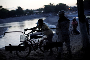 A man pushes a bicycle next to a member of Mexican security forces on the bank of the river Suchiate in Ciudad Hidalgo