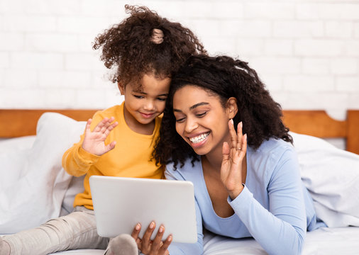 Mother And Daughter Using Tablet Making Call Lying In Bed