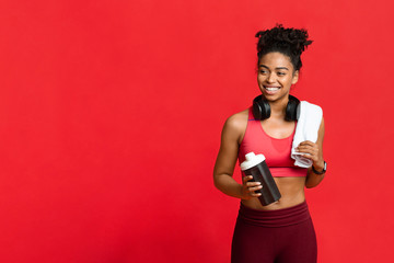 Happy fitness afro girl drinking protein during exercising