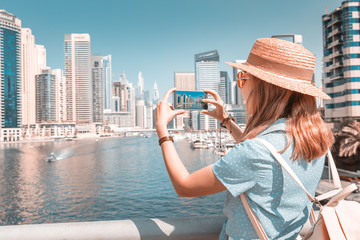 Happy Asian tourist girl taking photos in popular Marina district in Dubai for her social media and blog