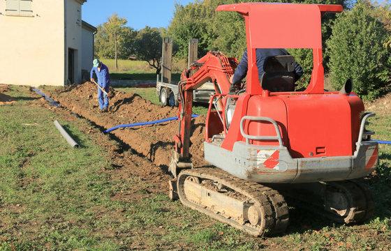 Pose des tuyaux dans la tranchée de raccordement d'une maison.