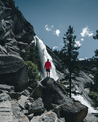 An adventurous guy standing in front of a huge waterfall in the Yosemite Valley. People who adventure. Instagram format photograph