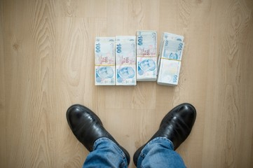 High angle shot of a person standing next to stacks of money on a wooden surface