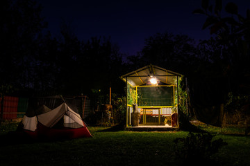 Tents versus shelter. Camping spot with white red tent and mini shelter house in the campground surounded by nature  at night. No person.