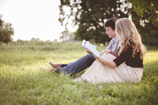 Couple reading the bible together in a garden under sunlight with a blurry background