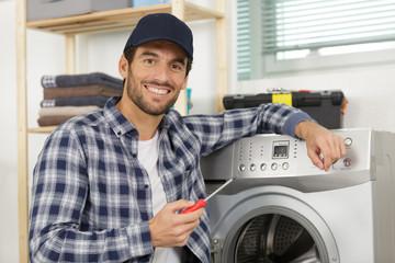 working man plumber repairs a washing machine in laundry
