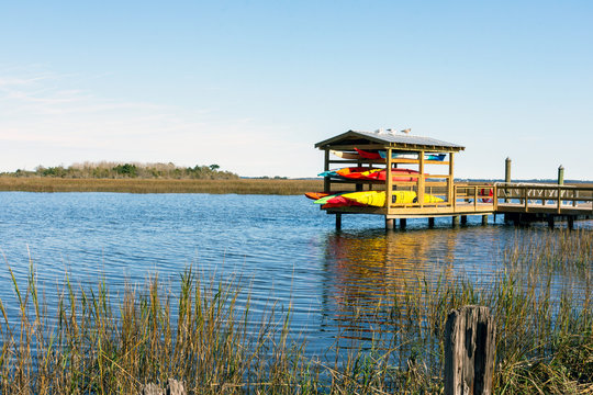 Colourful kayaks are stored on a dock overlooking the beautiful lowcountry salt marsh between Jekyll Island and St. Simons Island, Georgia, in the southeastern United States.