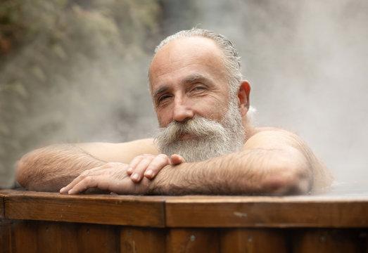 Bearded senior man enjoying outdoor bathing in winter.