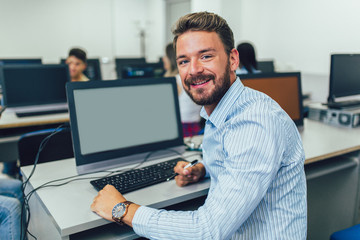 Man working on computer in computer lab.