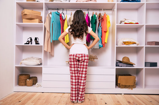 Dressing for success. Full-length photo of a young girl in pajamas, who is standing with her back to the camera and her hands on hips, looking at clothes in her wardrobe.