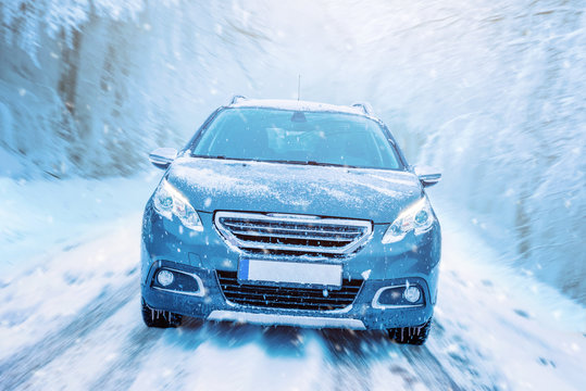 Car drives through the snow. Winter driving concept. Road and trees in motion. Front view of the car on the road