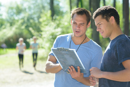 sports instructor talking with male sportsman outdoors