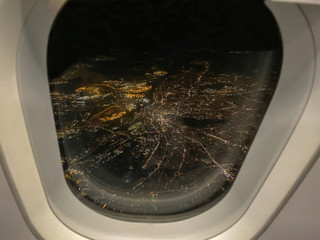 Nightview out of airplane window with illuminated big city